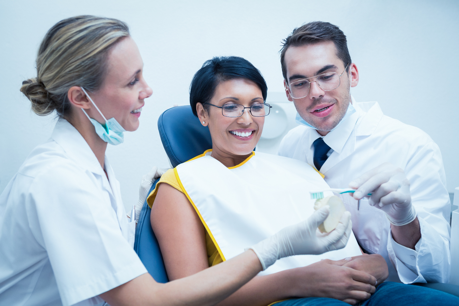 Male dentist with assistant showing woman how to brush teeth in the dentists chair